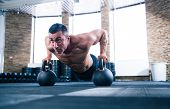 image of kettles  - Handsome muscular man doing push ups on kettle ball in crossfit gym - JPG