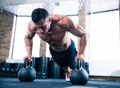 foto of kettles  - Handsome muscular man doing push ups on kettle ball in crossfit gym - JPG