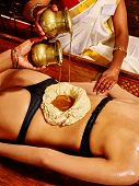foto of ayurveda  - Young woman having stomach Ayurveda spa treatment - JPG