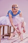 image of ballet shoes  - Professional ballerina putting on her ballet shoes on the wooden floor on a pink background - JPG