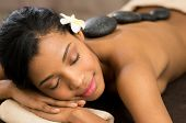 picture of black woman spa  - Beautiful young woman with eyes closed receiving hot stone massage at salon spa - JPG
