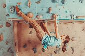foto of climbing wall  - Young woman training on practice climbing wall indoor - JPG