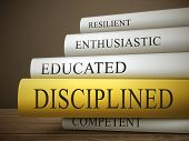 stock photo of discipline  - book title of disciplined isolated on a wooden table over dark background - JPG
