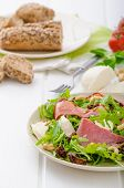 stock photo of baguette  - Arugula salad with smoked rump sundried tomatoes cashew nuts and mozzarella wholemeal baguette - JPG