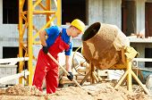 stock photo of shovel  - builder man working with shovel during concrete cement solution mortar preparation in mixer at construction site - JPG