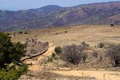 picture of dirt road  - Dirt road in the mountain and mountain bikers on it - JPG