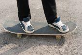 picture of skateboarding  - Skateboarder feet in sneakers on a skateboard - JPG