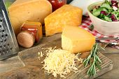foto of grating  - Grated cheese on wooden cutting board - JPG