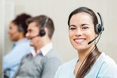 picture of telemarketing  - Portrait of smiling female customer service agent with colleagues in background at office - JPG