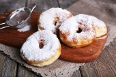 pic of icing  - Delicious donuts with icing and powdered sugar on wooden background - JPG