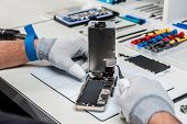 picture of stolen  - Technician replacing the screen of a used smartphone - JPG