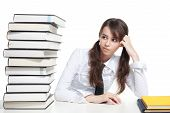 image of teen pony tail  - Girl sitting with pile of books and thinking - JPG