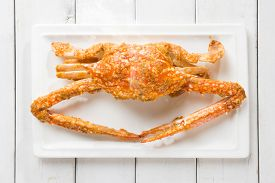 stock photo of cooked crab  - Close up top view cooked delicious hot and spicy sauce blue crab on white plate - JPG