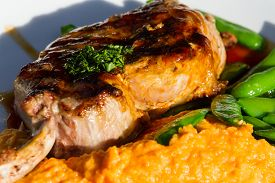 stock photo of sweet pea  - french cut pork chop served with a sweet potato puree and green peas on a white plate - JPG