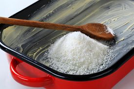 foto of grease  - heap of desiccated coconut in greased baking pan - JPG