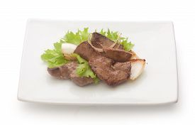 stock photo of liver fry  - Fried pieces of beef liver with fresh green lettuce basil and fried onion on the white plate  - JPG