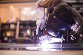 stock photo of welding  - Worker welding aluminum using tig welder in factory - JPG