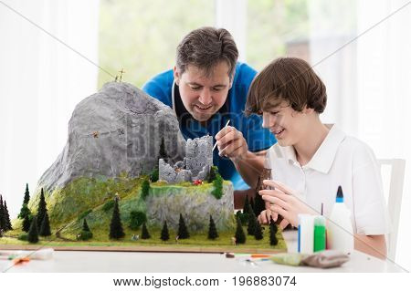poster of Father and son work on model building school project. Kids and parent build miniature scale model mountain for geography class. Extracurricular activities and family hobby. Art and crafts for child.
