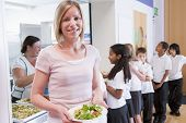 Students in cafeteria line with teacher holding her healthy meal and looking at camera