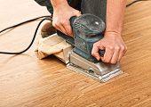 detail of carpenter use sander on wood floor