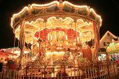 Imagem borrada / longa exposição de um passeio de cavalo de carrossel brilhantemente iluminada