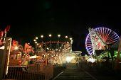 Imagem borrada / longa exposição de um parque de diversões brilhantemente iluminada passeios no calçadão