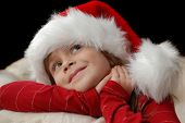 A beautiful young girl wearing a santa hat thinking about christmas