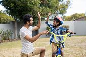 Father and son doing high five while cycling in yard poster