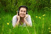 Mädchen mit Kopfhörern im Gras liegend