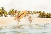 Two Beautiful Surfer Girls At The Beach Go Into The Water. poster