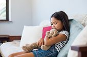 Smiling young girl sitting on couch and embracing her teddy bear. Asian cute little girl hugging stu poster