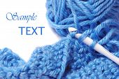 Blue silky yarn with crochet hook and completed stitches on white background with copy space.  Macro