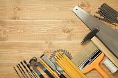 Working tools on a wooden boards background. Including saw, ruler, drill, nails, pliers,hammer, brush,thread,chisel.