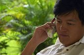 Asian Male Listening Intently On The Phone