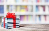 Books with ribbon bow as gift on wooden table at library poster