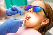 Dentist examining teeth of elementary age girl in pediatric dental clinic using dental tool and angl poster