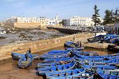 Essaouira Ramparts Aerial Panoramic View In Essaouira, Morocco With Traditional Blue Fishing Ships.  poster