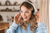 Portrait of joyful blond girl 20s wearing headphones smiling and rejoicing while listening to music  poster