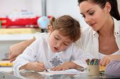 stock photo of babysitting  - Teacher watching her pupil coloring a drawing - JPG