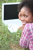 Young woman with a blank screened laptop in the grass