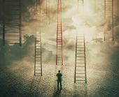 Man Standing In Front Of Huge Ladders Going Up To The Sky. Choosing A Different Red Stairway To Unkn poster