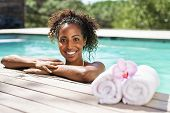 Smiling young black woman at swimming pool edge with rolled up towel. Portrait of beautiful african  poster