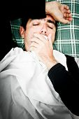 Dramatic desaturated image of a sick man laying in bed and coughing with a handkerchief in his hand