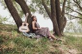 Hippie Woman With Guitar Sitting Near A Tree In The Forest poster
