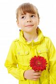Pleading sweet little girl wearing yellow jacket standing and holding red flower