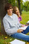 Joyfull sorridente rapaz adolescente e bocejar menina sentado sob a árvore com livros e cadernos no Parque Outono