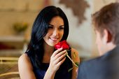 foto of amor  - Young happy couple romantic date at restaurant, celebrating valentine day man give red rose to his girl