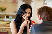 picture of amor  - marriage proposal, man give ring to his girl, young happy couple romantic date at restaurant, celebrating valentine day