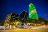 BARCELONA - NOVEMBER 24: Torre Agbar office building, illuminated at night, with traffic lights, on
