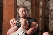 foto of choke  - Blond mixed martial arts fighter being choked from behind - JPG